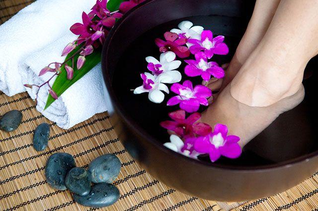Pés dentro de bacia com flores