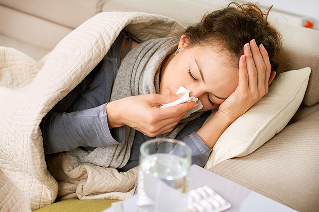 Mulher com gripe assoando o nariz