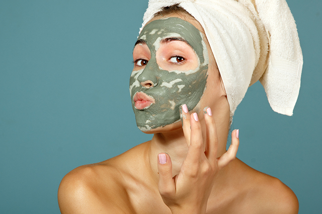 Mulher com máscara facial de argila verde
