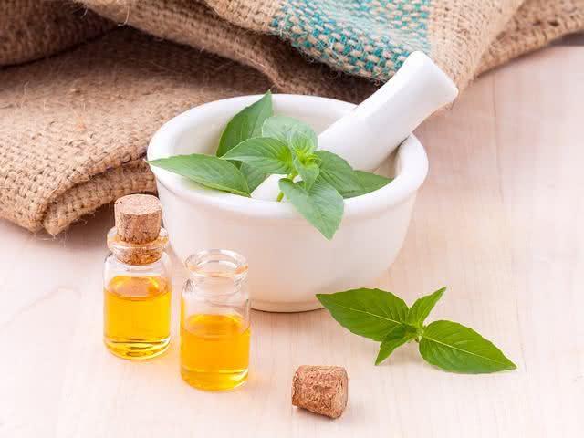 Folhas de ervas e vidros com óleo medicinal