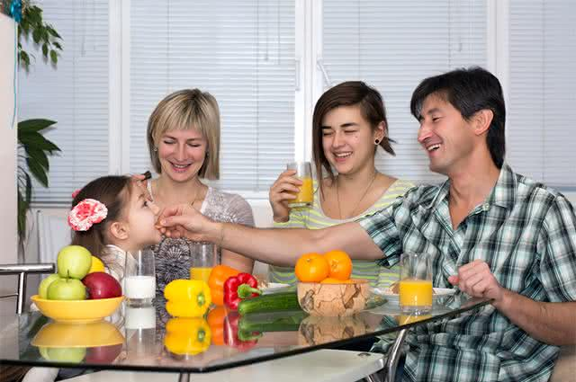 Imagem de família reunida comendo frutas e verduras