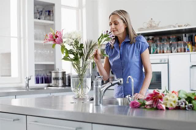 Mulher cheirando flores em cozinha de casa