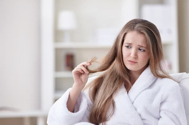 Mulher segurando em pontas dos cabelos