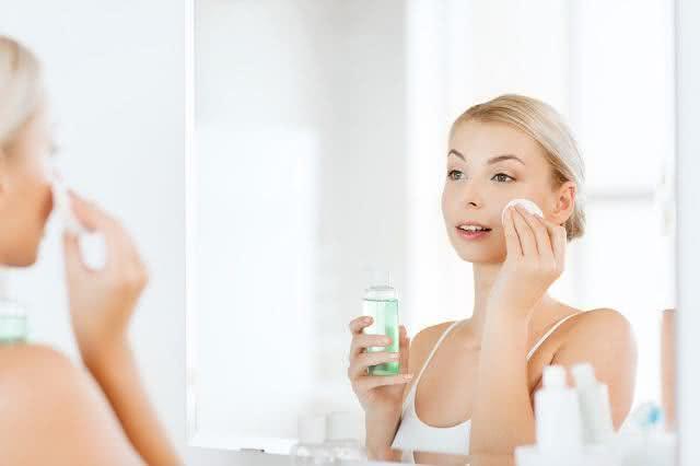 Imagem de mulher passando tônico no rosto