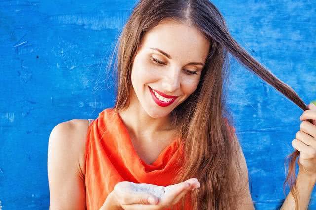 Imagem de mulher segurando e olhando para shampoo seco na palma da mão