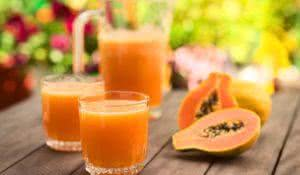Two glasses of freshly prepared papaya juice with pitcher and papaya fruits in the back on table outdoors (Selective Focus, Focus on the front rim of the first glass)
