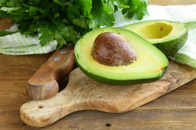 Imagem de abacate em tábua de cortar e ao lado de faca