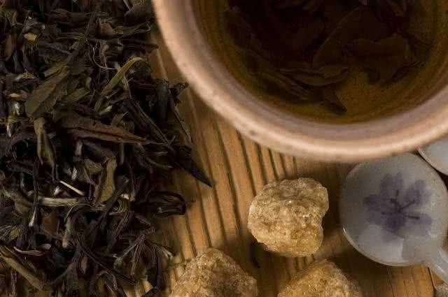 Imagem de ervas de chá verde e caneca com o líquido