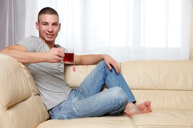 Imagem de homem jovem em sofa tomando chá