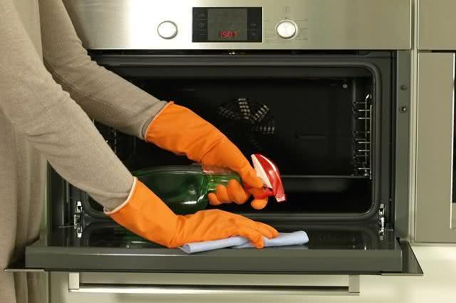 Imagem de mulher limpando o forno