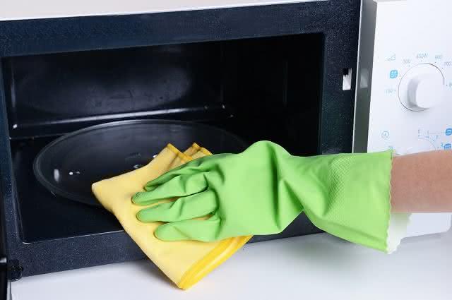 Imagem de mulher limpando micro-ondas com pano