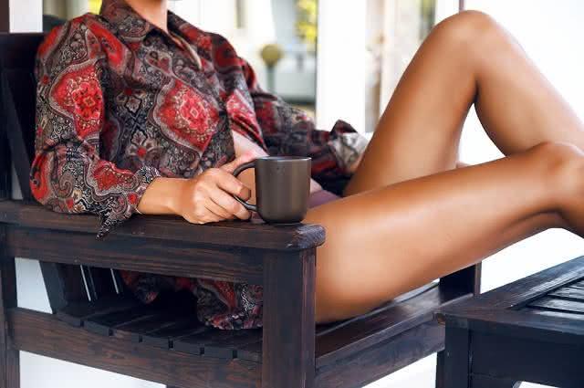 Imagem de mulher morena sentada em cadeira com caneca de chá