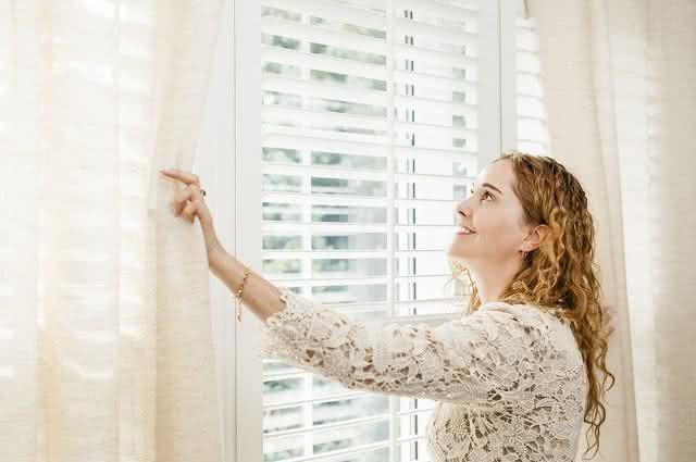 Imagem de mulher tocando e olhando para cortina de renda