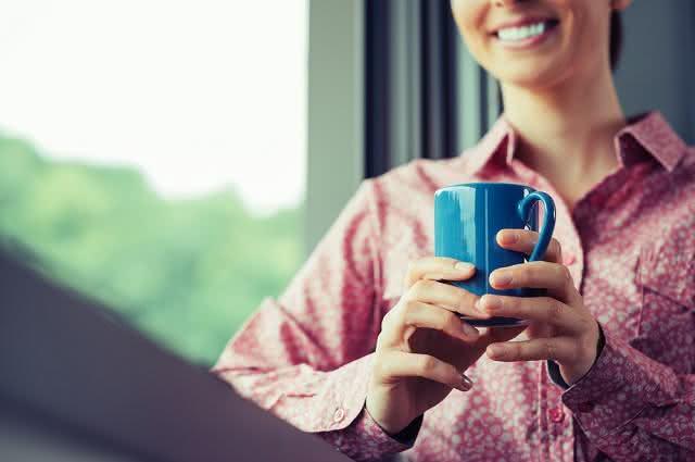 Imagem de mulher próximo de janela segurando caneca azul