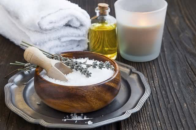 Imagem de óleo de banho, toalha, copo de vidro e tigela com sal grosso