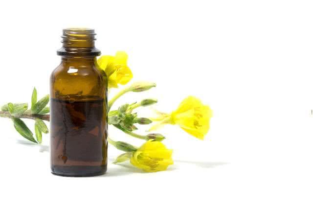Imagem de vridro de óleo próximo de flores de prímula