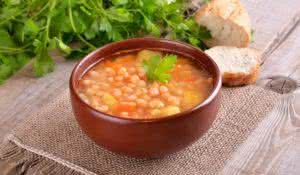 Bean soup in ceramic bowl on wooden table