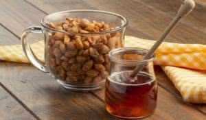 A glass cup of honey roasted peanuts on a wooden table, a yellow checkered napkin and a honey jar