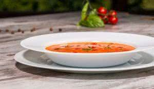 Close-up low-angle picture of cold tasty tomato soup gazpacho with species on the wooden table in vegan cafe with tomatoes standing near a plate, with copy place and selective focus on a plate