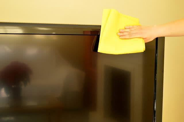 Imagem de mão limpando TV