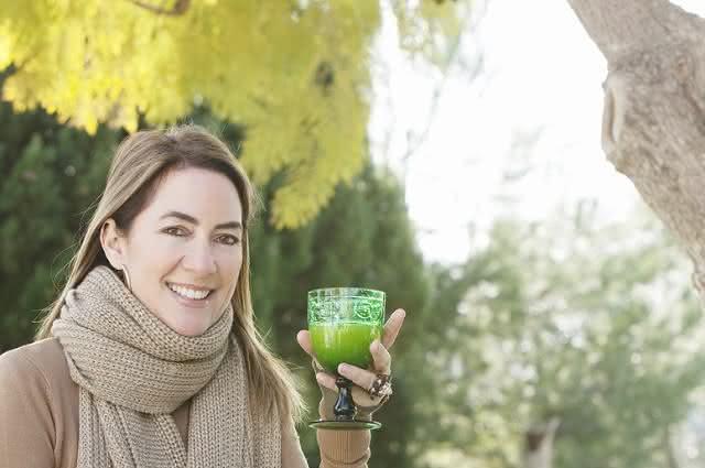 Imagem de mulher de agasalho tomando suco em dia frio