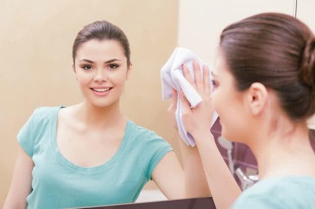 Imagem de mulher limpando espelho