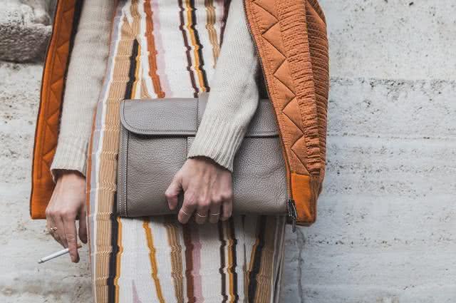 Imagem de mulher segurando cigarro e bolsa