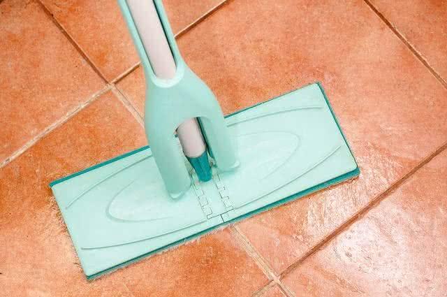 Imagem de rodo limpando cerâmica em piso