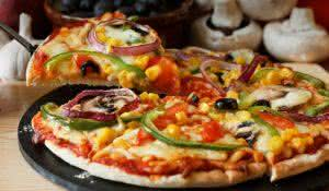 Vegetarian pizza slice with a topping of Mushroom, Tomatoes, peppers, onions, sweetcorn and olives