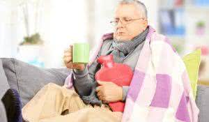 Ill middle aged man on a sofa covered with blanket drinking hot tea at home