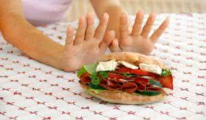 female hands refusing big meat sandwich with ham and cheese