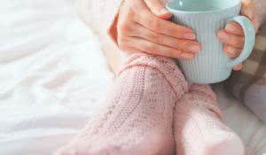 Woman relaxing at cozy home atmosphere on the bed. Young woman with cup of milk in hands enjoying comfort. Soft light and comfy lifestyle concept.