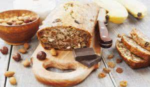 Banana cake with raisins, nuts and chocolate on the wooden table