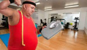 Large unhappy fitness man with weight scale in a gym