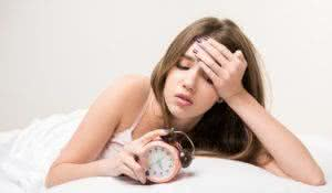 What a long night. Young beautiful woman lying in bed and looking at clock failing to fall asleep