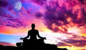 Yoga meditation in lotus pose by man silhouette with moon and purple dramatic sunset sky background. Free space for text and can be used as template for web-sit