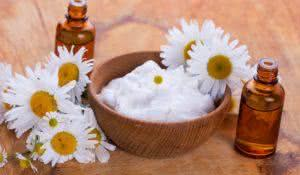 Beauty cream in bowl  with chamomile on wooden background. Selective focus, horizontal.