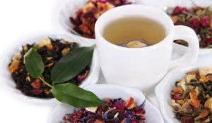 Cup of tea with aromatic dry tea in bowls close up