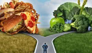 Diet decision concept and nutrition choices dilemma between healthy good fresh fruit and vegetables or greasy cholesterol rich fast food with a man on a crossroad trying to decide what to eat for the best lifestyle choice.