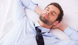 Businessman sleeping. Top view of handsome young man in shirt and tie holding hands behind head while sleeping in bed