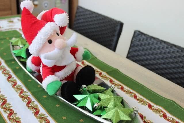 Estrela natalinas com pequeno papai noel sobre a mesa.
