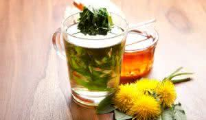 herbal tea with fresh dandelion leaf inside teacup and yellow blossoms, on wooden table