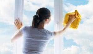 Young woman washing windows