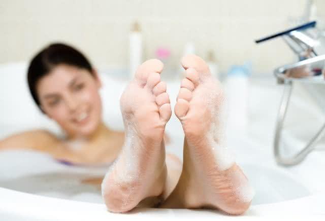 Pés sendo lavados numa banheira.