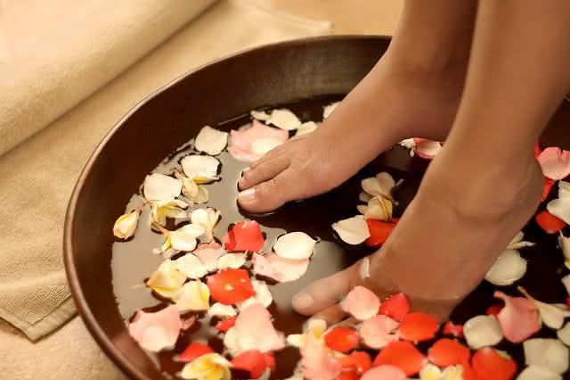 Pés sendo lavados numa bacia com flores.