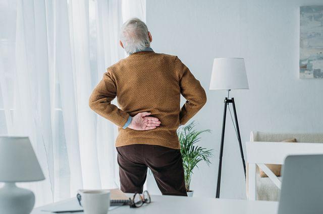 Idoso sentindo dor na lombar que é um dos sintomas da osteoporose