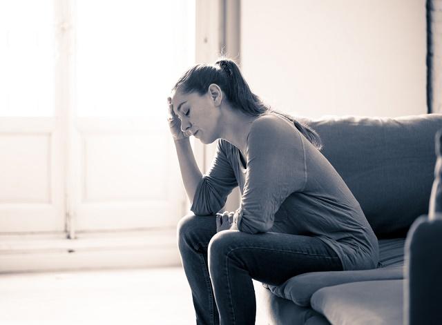 Mulher sentada com mão na cabeça