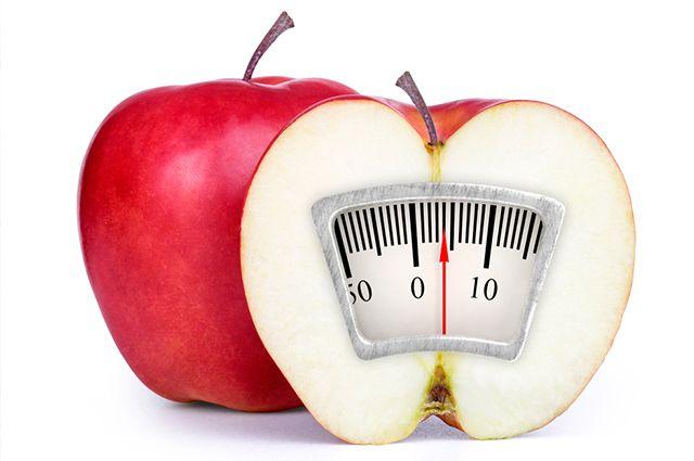 Imagem de maçã cortada ao meio com uma balança em seu interior