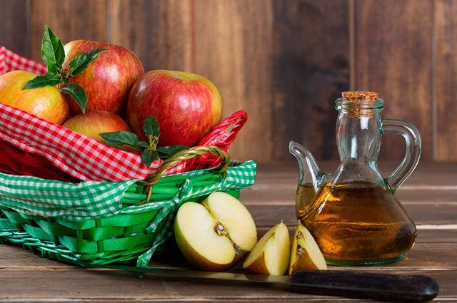 Frasco de vinagre de maçãs junto a algumas maçãs