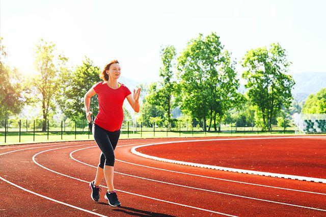 Mulher grávida correndo em uma pista de corrida